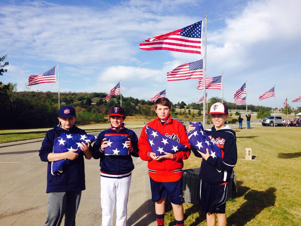 Cj Mumme, Max Diaz, Zach Wood and Garrett Duncan raise flags for Memorial Day Weekend